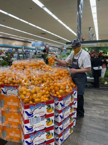 Daniel Judge stocks a citrus display in the Gelson's Sherman Oaks store.