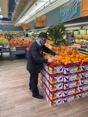 Mike Sockett arranging oranges in the Gelson's North Hollywood store.