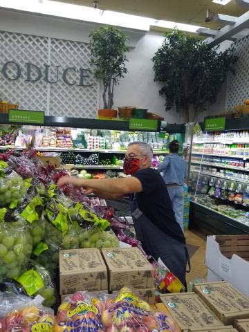 Otto Gomez stocking grapes in the Gelson's Hollywood store.